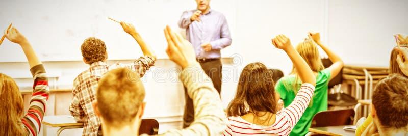 Studenter som lyfter händer i klassrum arkivbilder