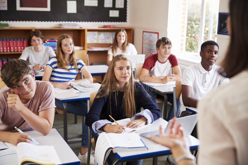 Studenter som lyssnar till lärarinnan In Classroom arkivfoton