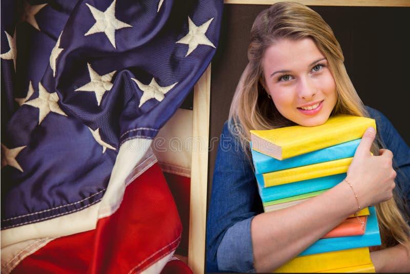 studenter som rymmer böcker mot amerikanska flagganbakgrund arkivfoto