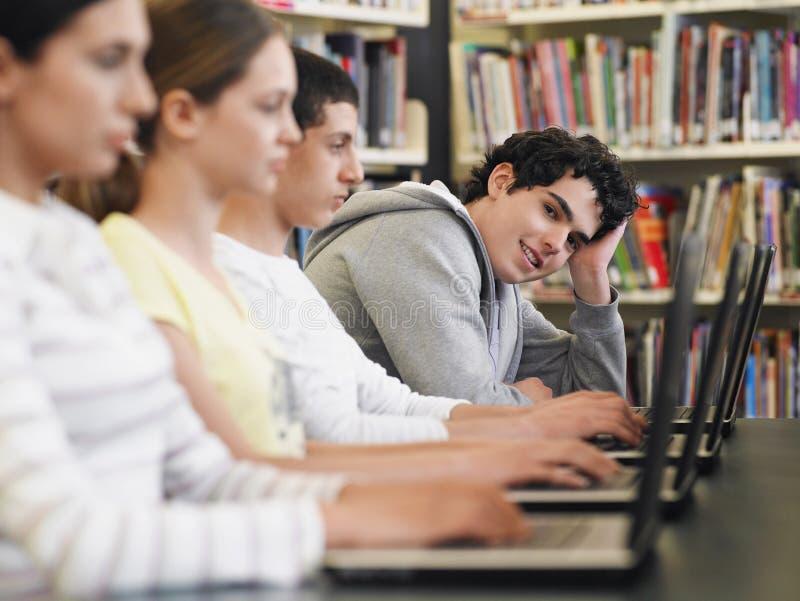 Studenter som sitter i rad genom att använda bärbara datorer i arkiv royaltyfria foton