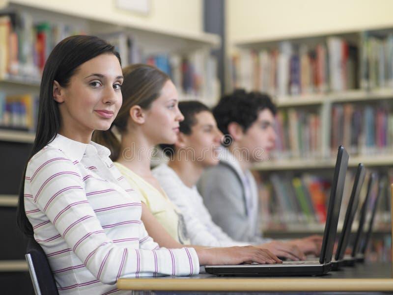 Studenter som sitter i rad genom att använda bärbara datorer i arkiv royaltyfri bild