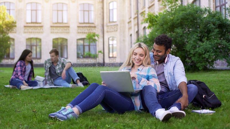 Studenter som sitter på gräs och den hållande ögonen på roliga videoen på bärbara datorn, underhållning arkivfoto