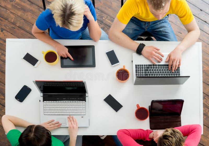 Studenter som sitter på tabellen genom att använda datorer royaltyfria foton