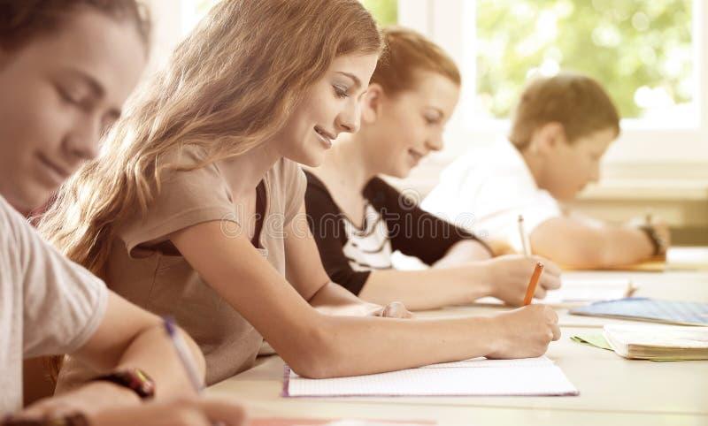 Studenter som skriver ett prov i skolagrupp royaltyfri fotografi