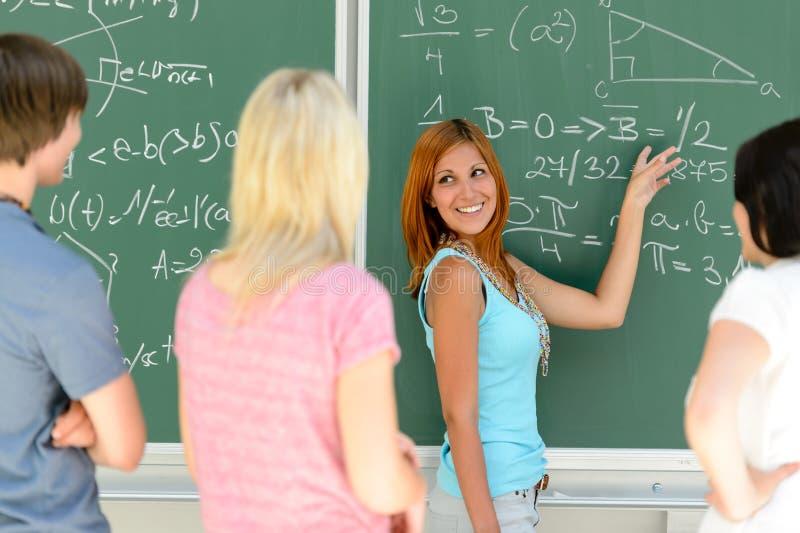 Studenter som står framdelen av grön svart tavlamatematik arkivfoton