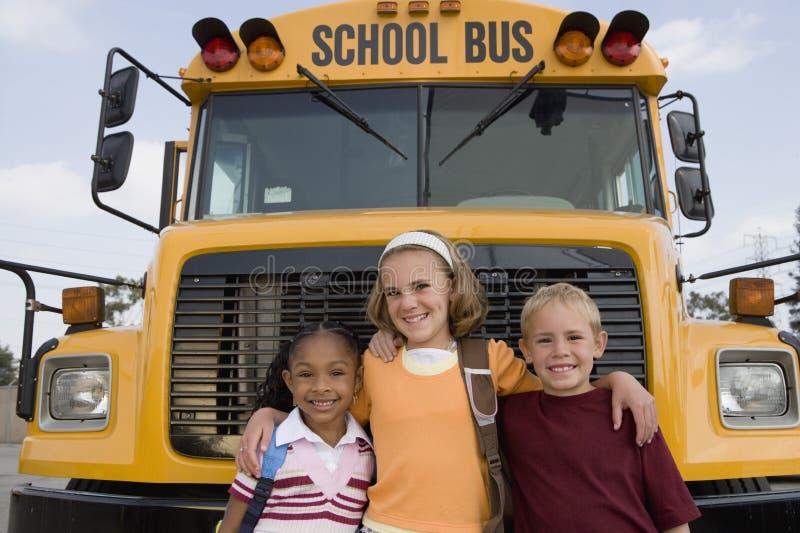 Studenter som står i Front Of School Bus fotografering för bildbyråer