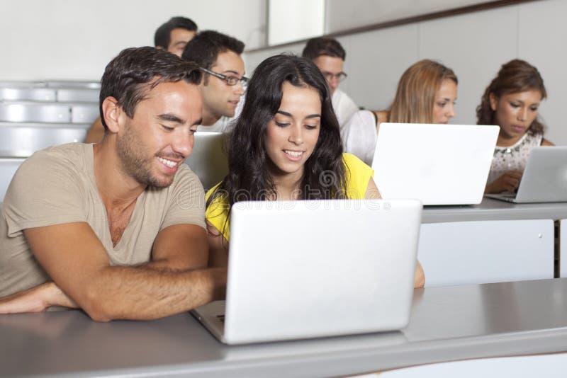Studenter som studerar med bärbara datorn i grupprum royaltyfri bild