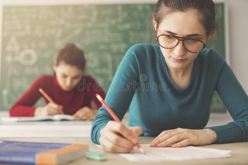 Studenter som tar examenhandstilsvar i klassrum arkivfoto