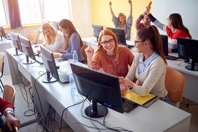 Studenter som tillsammans sitter på tabellen genom att använda datoren i grupp på universitetsområde royaltyfri foto