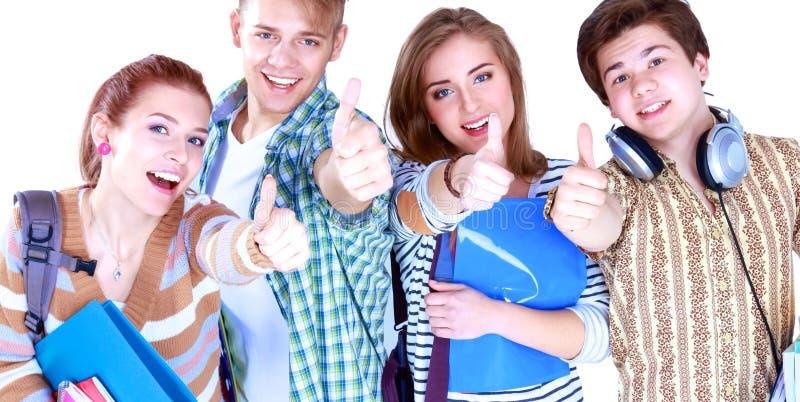 Studenter som tillsammans står och visar tummar-upp royaltyfri foto