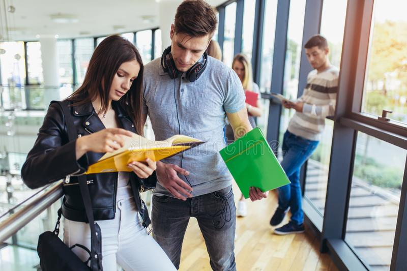 Studenter som tillsammans studerar i korridoren av universitetet arkivbilder