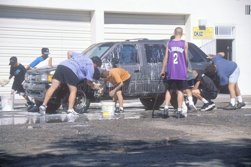 Studenter som tvättar bilar för en skolafundraiser, NM royaltyfri bild