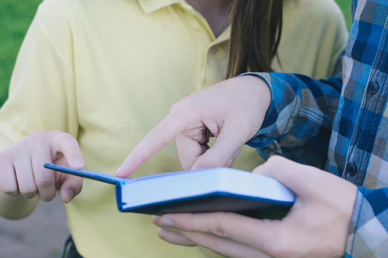 Studenter som utomhus studerar och rymmer böcker arkivfoton