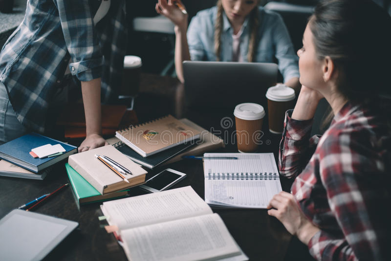 Studentes die koffie drinken en samen bij lijst bestuderen stock foto