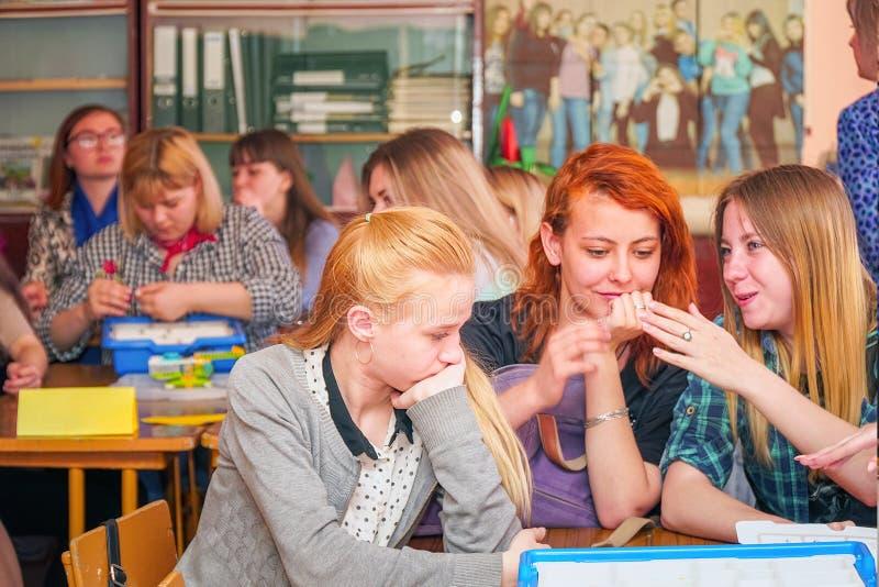 Studentes in het klaslokaal bij hun bureaus royalty-vrije stock afbeelding