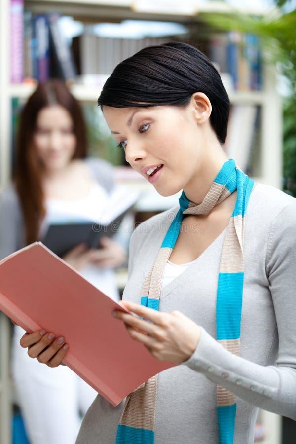 Studentessa alla biblioteca contro gli scaffali per libri fotografia stock libera da diritti