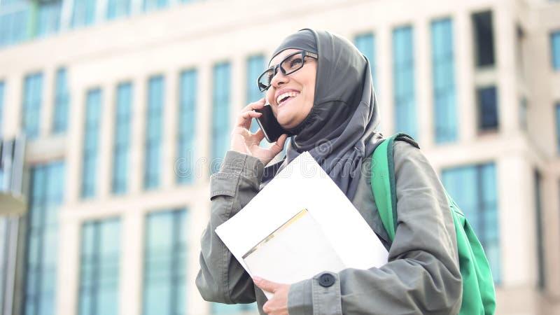 Studentessa araba allegra che parla sulla condizione del telefono sul campus universitario fotografia stock