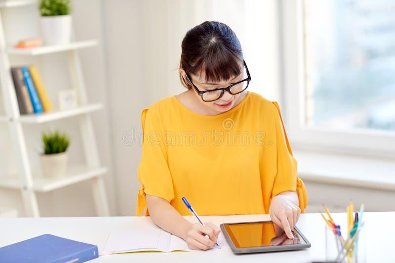 Studentessa asiatica con il pc della compressa a casa fotografie stock