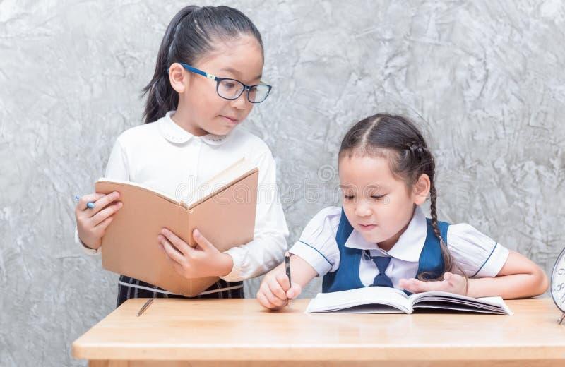 Studentessa asiatica sveglia nella scrittura uniforme il suo compito fotografie stock