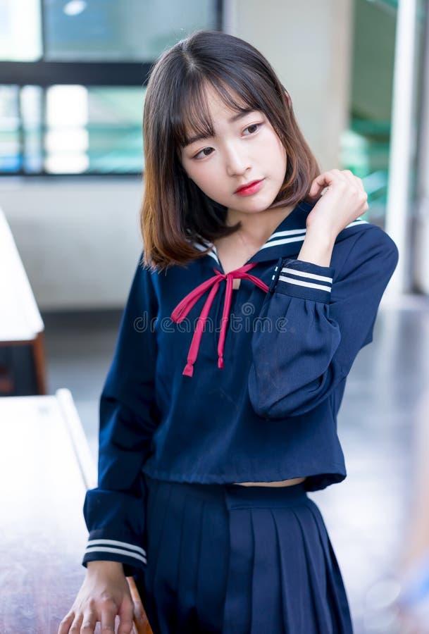 Studentessa asiatica in uniforme scolastico che impara nell'aula fotografia stock libera da diritti