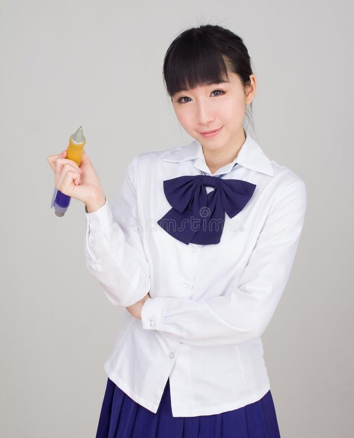Studentessa asiatica in uniforme scolastico che studia con una penna di palla di grande misura fotografia stock libera da diritti