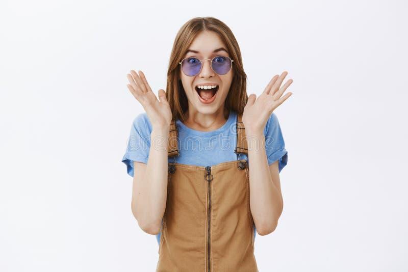 Studentessa attraente entusiasta sorpresa in camici marroni ed occhiali da sole che alzano le palme vicino al fronte nella gioia  fotografie stock libere da diritti