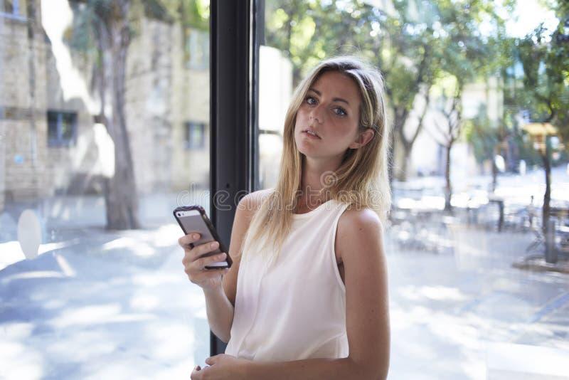 Studentessa bionda affascinante che chiacchiera sul suo telefono delle cellule durante la pausa fra le conferenze in università fotografie stock