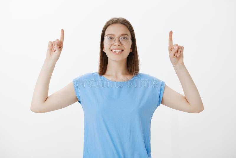 Studentessa bionda caucasica positiva in vetri, alzanti i dito indice ed indicanti su mentre sorridendo largamente fotografie stock libere da diritti