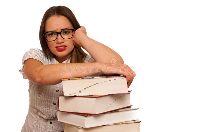 Studentessa caucasica asiatica sollecitata che impara nelle tonnellate di libri fotografie stock libere da diritti