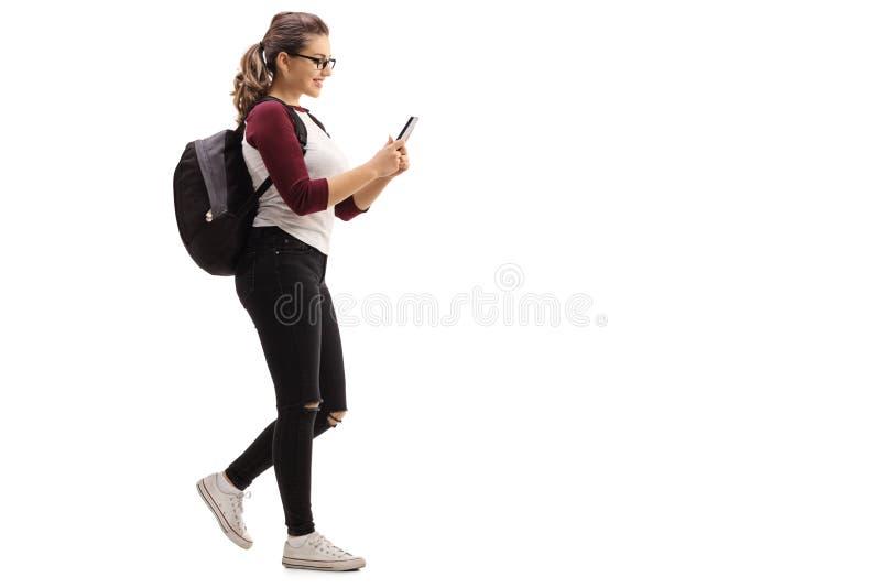 Studentessa che cammina e che esamina telefono cellulare fotografie stock libere da diritti