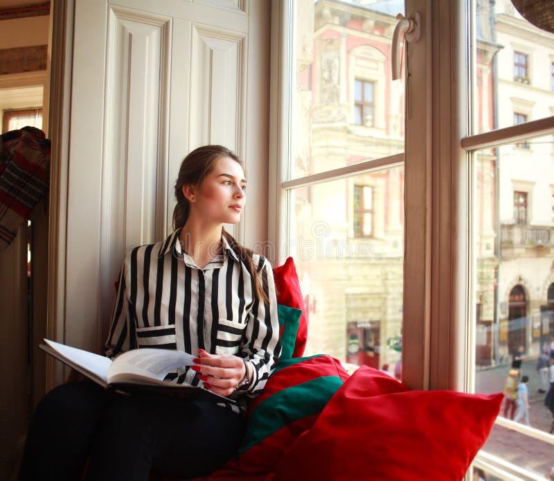 Studentessa che si siede a casa dalla finestra con il libro fotografia stock libera da diritti