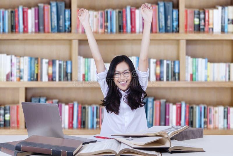Studentessa che solleva le mani in biblioteca mentre studiando fotografia stock libera da diritti