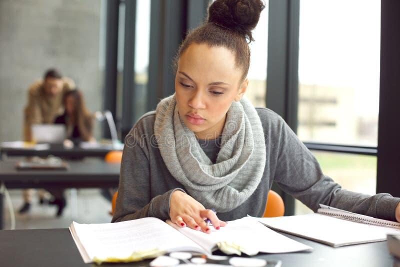 Studentessa che studia in una biblioteca fotografia stock
