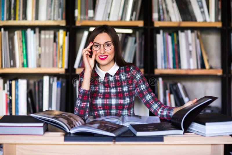 Studentessa con i libri di lettura di vetro nella biblioteca fotografia stock