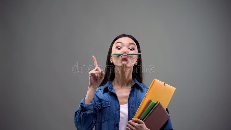 Studentessa con i taccuini divertendosi tenendo matita con le labbra, creativit? fotografie stock