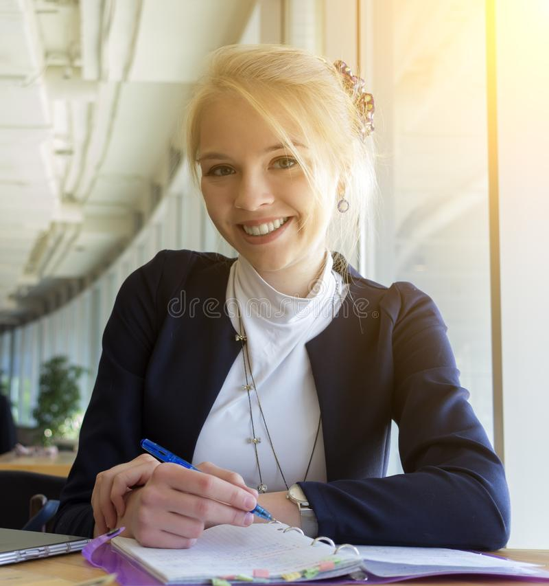 Studentessa dai capelli bionda sorridente che si siede nel pubblico, scrivente ed esaminante macchina fotografica fotografia stock libera da diritti
