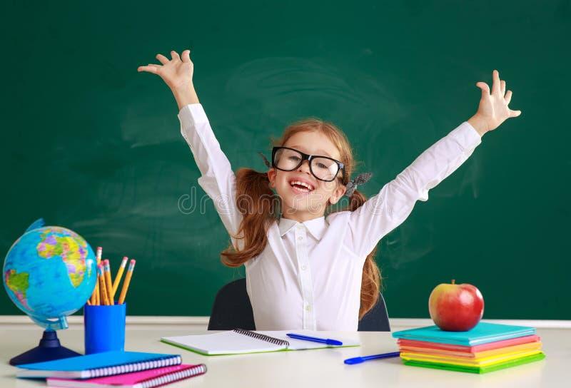 Studentessa della scolara del bambino circa la lavagna della scuola immagine stock libera da diritti
