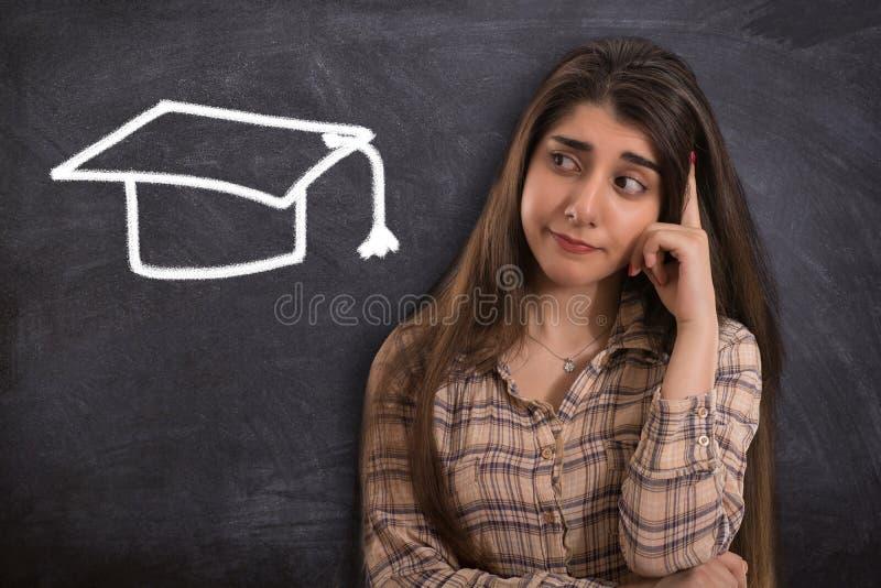 Studentessa di college che pensa con il cappuccio di graduazione fotografia stock libera da diritti