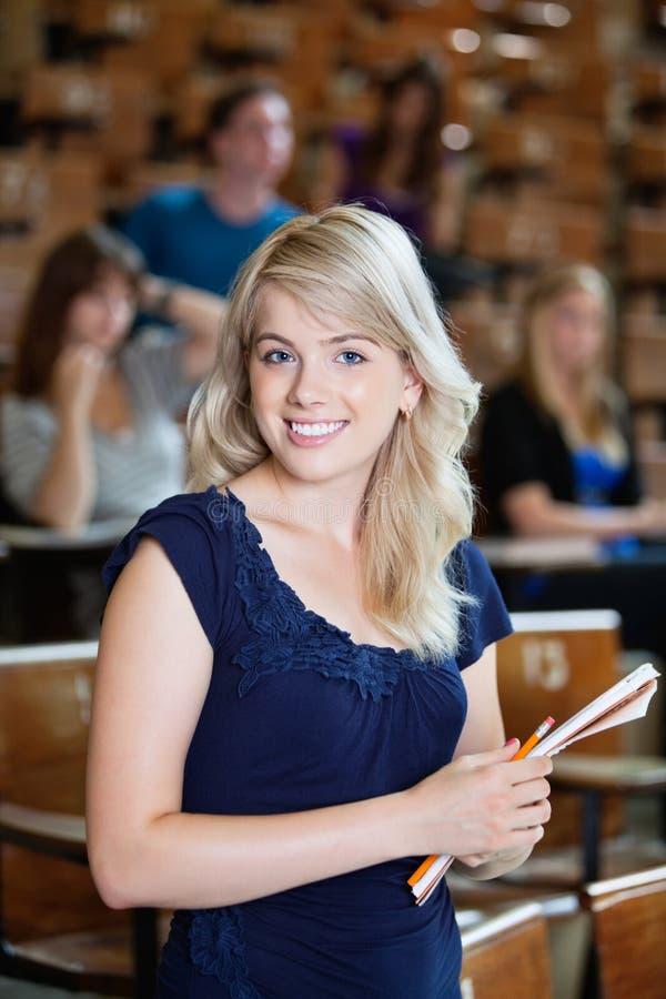 Studentessa di college che sta nella conferenza corridoio fotografia stock
