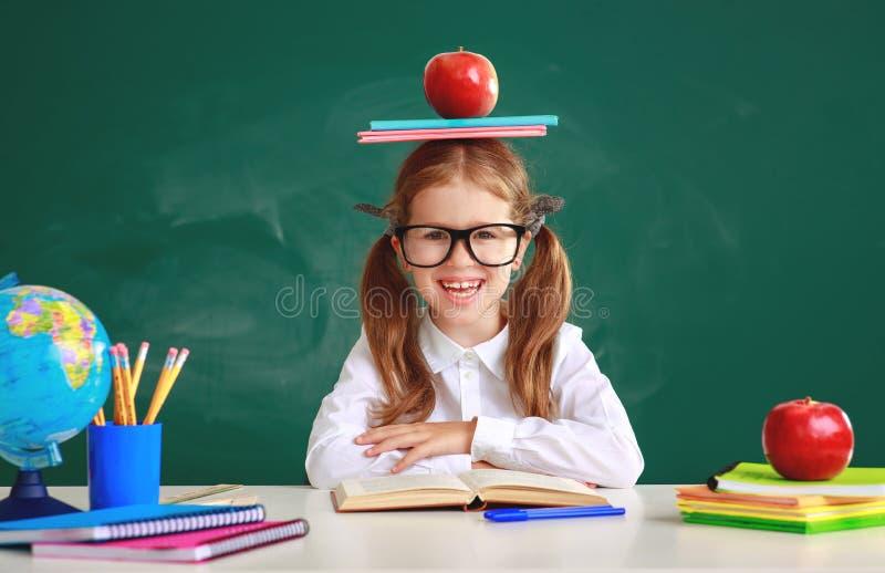 Studentessa divertente della scolara del bambino circa la lavagna della scuola immagine stock libera da diritti
