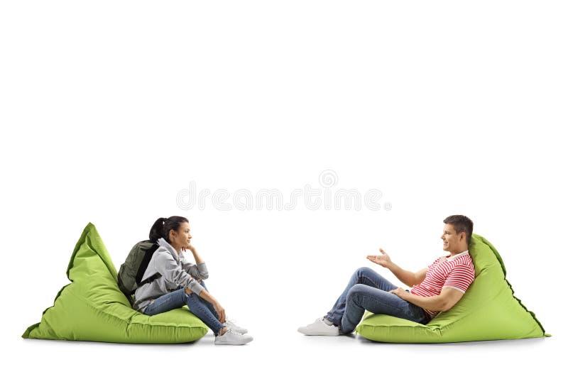 Studentessa e un giovane che si siede sulle borse e sulla conversazione di fagiolo immagini stock libere da diritti