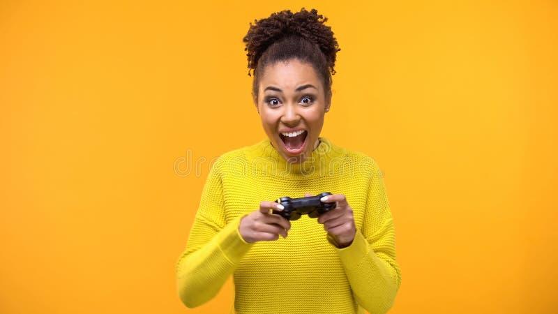 Studentessa felice con il fondo giallo della leva di comando del gioco, eccitazione di hobby fotografia stock libera da diritti