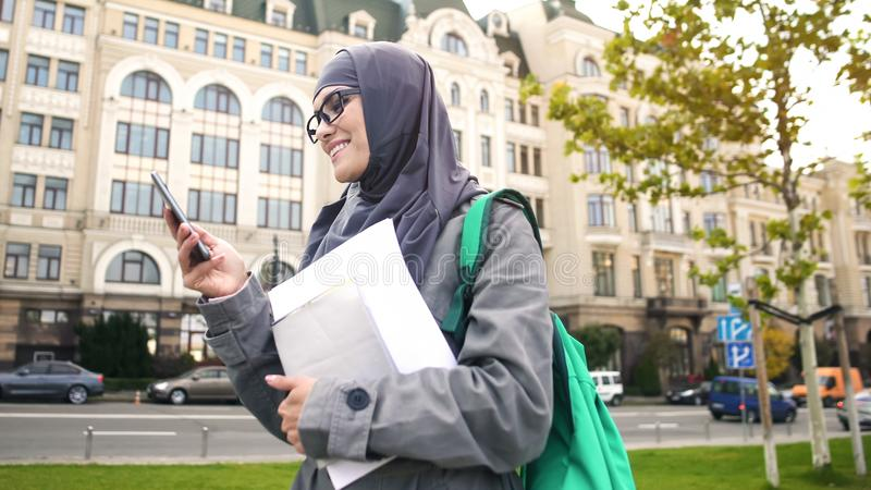 Studentessa musulmana sicura ispirata che chiacchiera sul telefono, stante sulla via fotografie stock libere da diritti