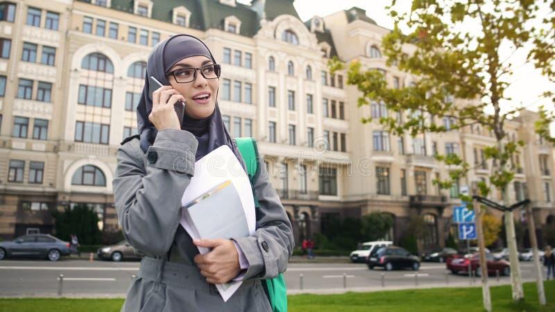 Studentessa musulmana sorridente sicura di sé che parla sulla condizione del telefono sulla via fotografie stock libere da diritti