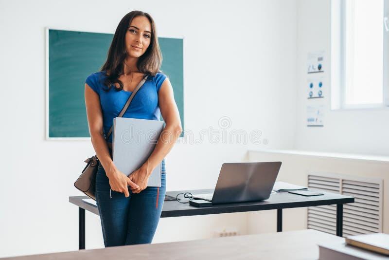 Studentessa nel libro e nel sorridere della tenuta dell'aula fotografia stock