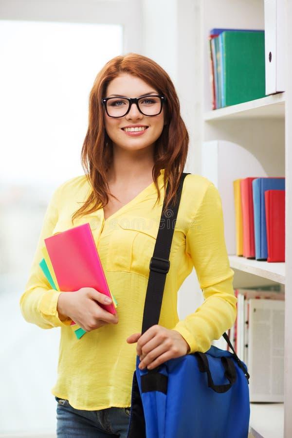 Studentessa sorridente con la borsa ed i taccuini immagine stock libera da diritti