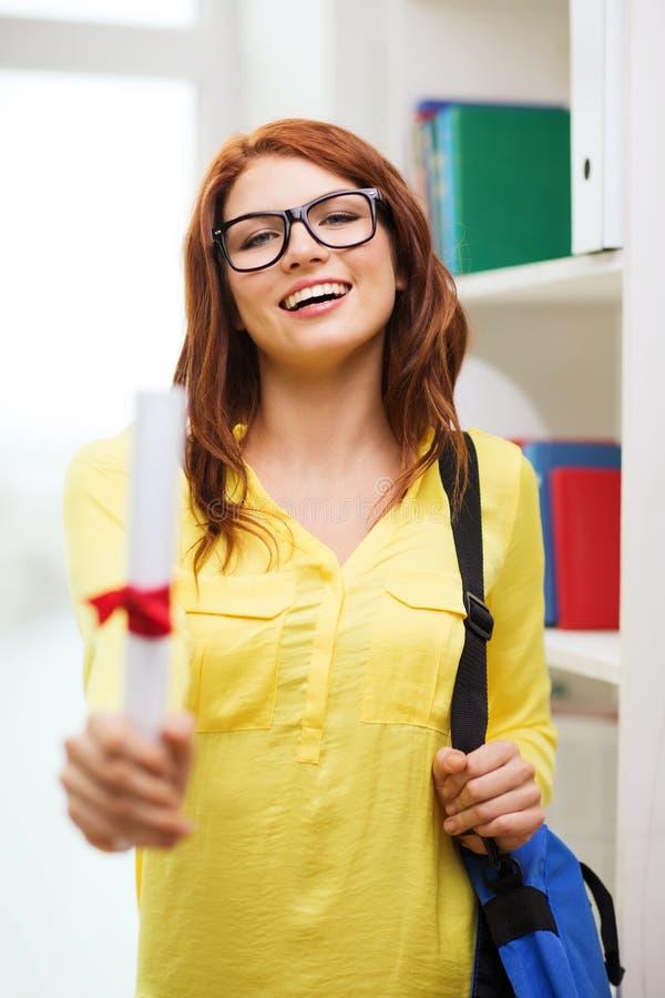 Studentessa sorridente con la borsa ed il diploma del computer portatile fotografia stock libera da diritti