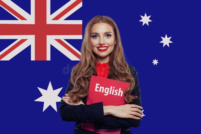 Studentessa sorridente felice con il libro contro il fondo australiano della bandiera Viaggio e istruzione in Australia fotografie stock libere da diritti