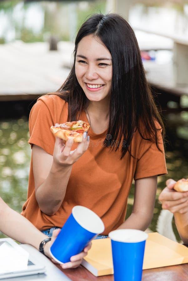 Studentesse asiatiche del ritratto che mangiano pizza con formaggio delizioso fotografia stock