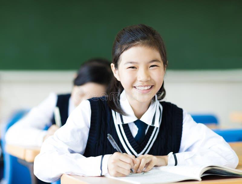 Studentflicka i klassrum och hennes vänner i bakgrund arkivfoto